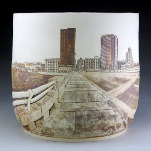 Melodee Jackson - Early January on the Pearl Street Bridge is a panoramic view of Grand Rapids, a city nearby my new home in America. When I displayed her, people talked about how the city had changed and about plans for change in the future. The vase is a memory of that place on a specific day in early January of 2017, captured permanently in stoneware. After graduating, I have never been back to RVA, the boarding school in Kenya where I grew up. I know that the home I knew no longer exists as it was. But I have memories.
